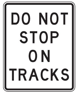 White rectangular sign with Do not stop on tracks in black letters