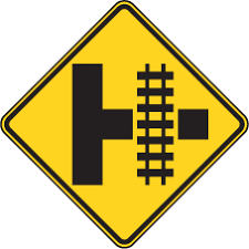 Yellow diamond sign with symbol for railway tracks crossing road