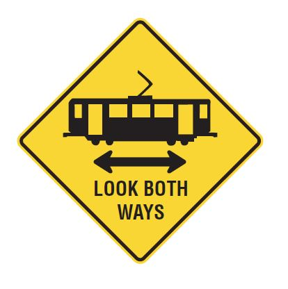 Yellow diamond sign with light rail car and double header arrow saying Look both ways