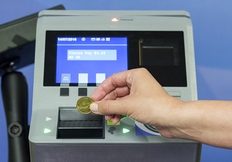 Hand inserting coin into coin slot of new farebox