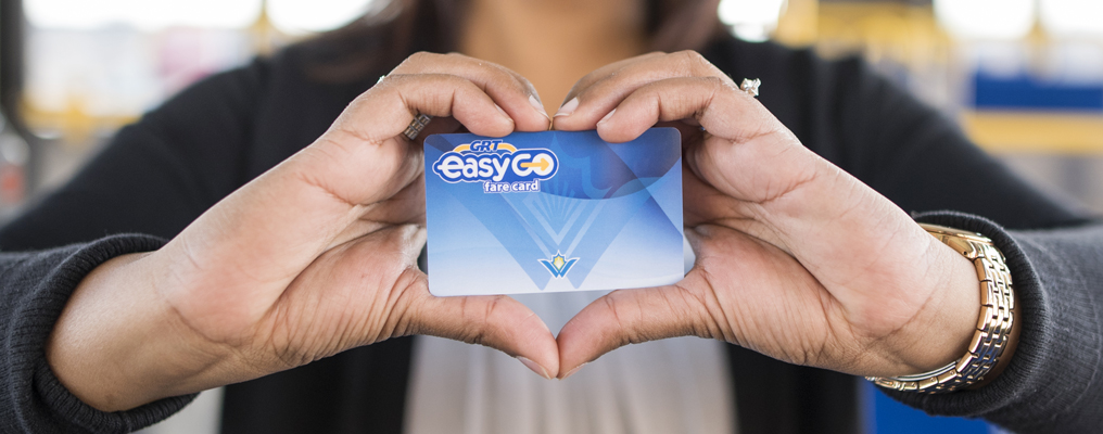 Hands holding fare card with fingers in shape of heart