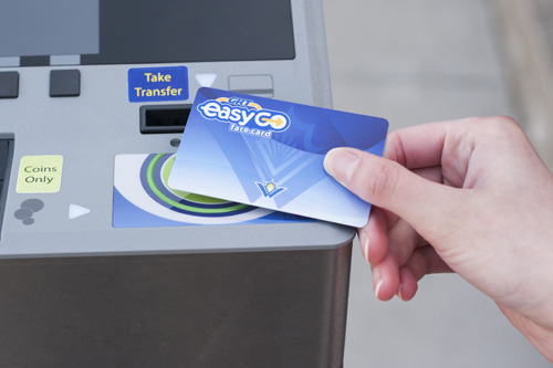 Hand holding EasyGO fare card to smart card target on farebox