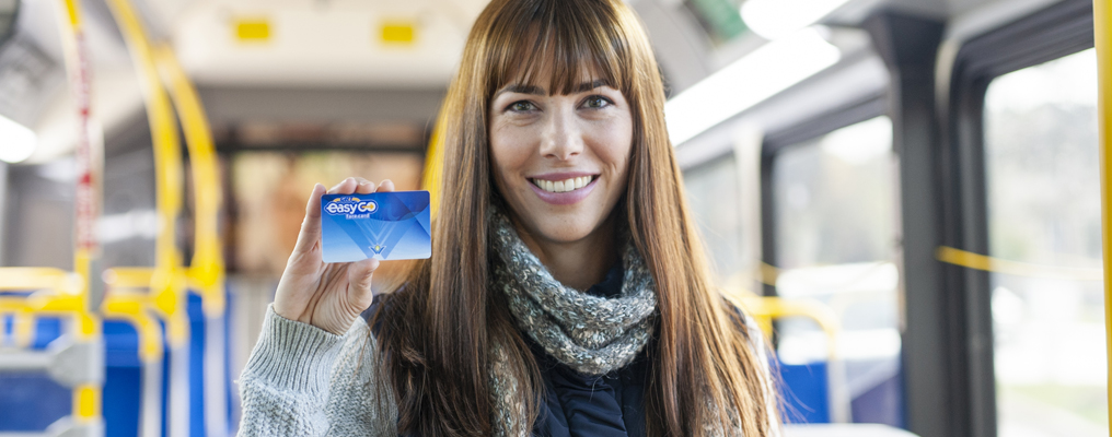 Smiling woman holding up fare card