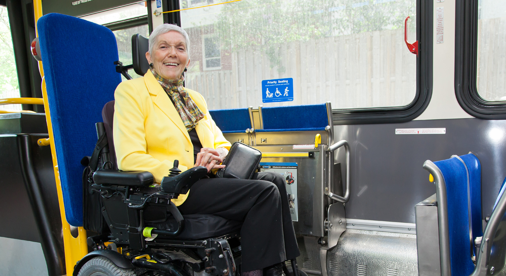 Woman in wheelchair seated in priority seating area at front of bus